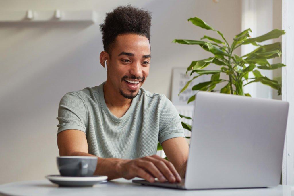 blij persoon op laptop