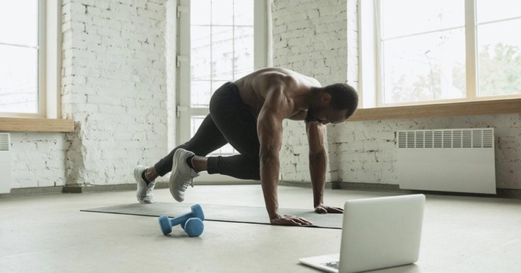 online fitness trainer man neemt sportles op